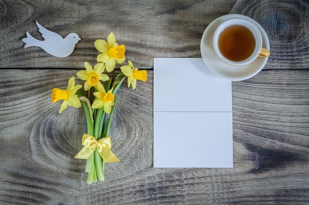Нарциссы с картой, птица и чашка чая на деревянных фоне. с днем матери,
