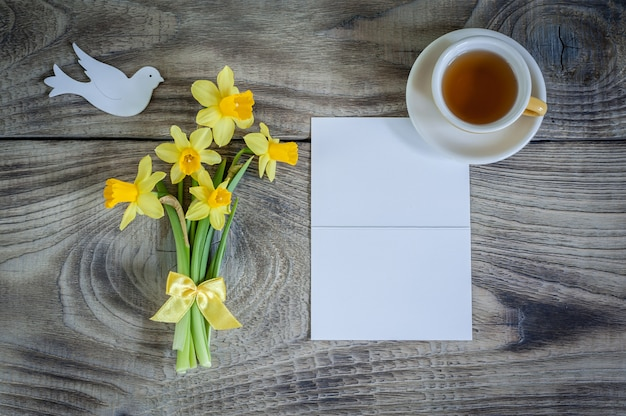 Daffodils with card, bird and cup of tea on wooden background. happy mother's day,
