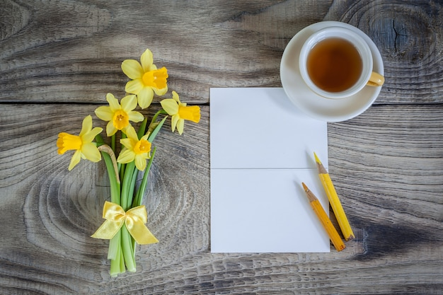 Daffodils with card and cup of tea . greeting card. happy mother's day, women's day or birthday. minimalism, top view, place for text.