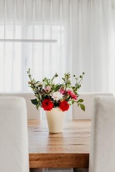 나무 식탁에 꽃병에 달리아 꽃 꽃다발. 밝고 통풍이 잘되는 현대적인 객실 인테리어.