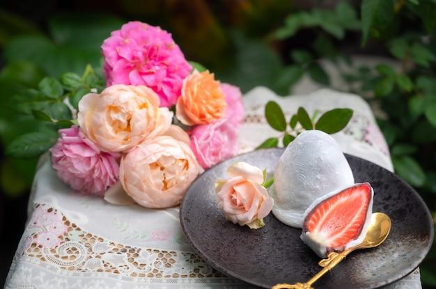 딸기로 속을 채운 다이후쿠, 형형색색의 장미 꽃과 장미 정원의 전망이 있는 테이블에 맛있는 일본 디저트.