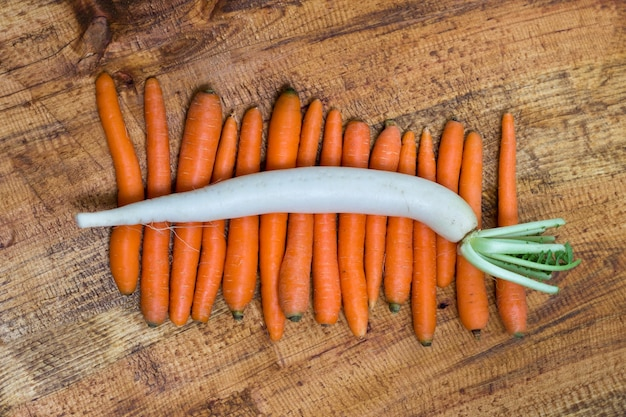 Daikon radish on carrots, wooden background