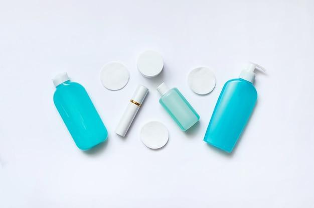 흰색 바탕에 데일리 케어 화장품입니다. 디스펜서, 병 및 항아리가있는 평평한 구성.