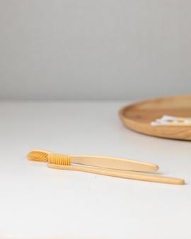 毎日の人間の衛生綿棒と綿棒は、竹の歯ブラシを持っている女性の手に