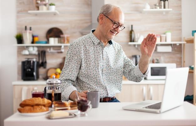 一杯のコーヒーを保持し、ウェブカメラで手を振っている甥とオンラインで話しているラップトップを使用して、朝食時にキッチンで年配の男性の日常生活。仮想会議、会議で在宅勤務の退職者