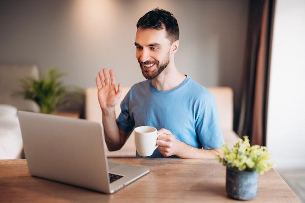 一杯のコーヒーを保持しているラップトップを使用してキッチンで若い男の日常生活