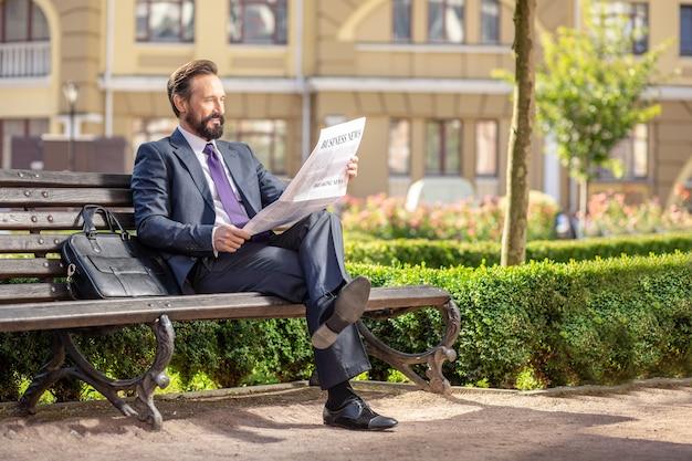 Ежедневные новости. полная длина приятного улыбающегося бизнесмена, читающего газету, сидя на скамейке