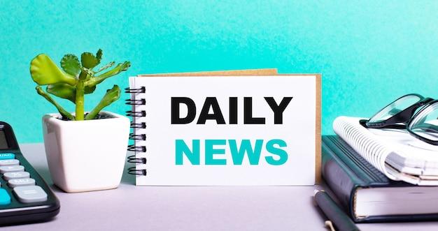 Daily newsは、鉢植えの花、日記、電卓の横にある白いカードに書かれています。組織の概念