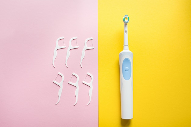 Daily oral hygiene for family. electrical toothbrush and dental floss on pink and yellow background top view, flatlay