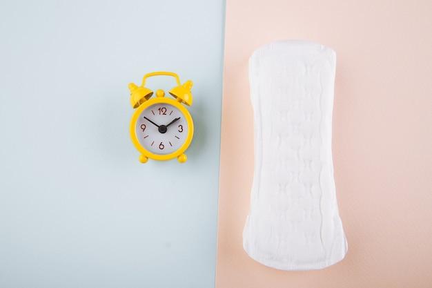 青ピンクの背景に毎日のパッドと黄色の目覚まし時計。女性の月経周期の概念。