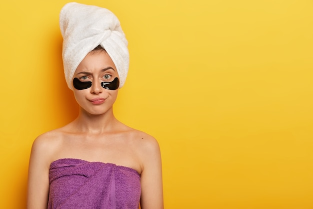 Daily pampering routine. lovely young female model wears under eye circles for removing dark circles, takes care of her skin, uses modern cosmetics