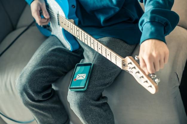 毎日の繰り返し。スマートフォンを膝の上に置きながら楽器をチューニングし、受信したメッセージを観察する勤勉なミュージシャン