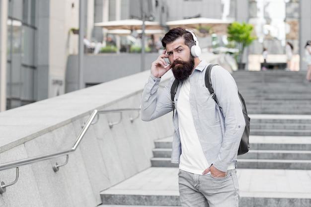 仕事への毎日のルート。現代の生活。市内中心部を歩くヘッドフォンを持つ男。音楽を聴く。景観コンセプトの変更。通りを歩くバックパックとハンサムなヒップスター。空の通りを歩く。