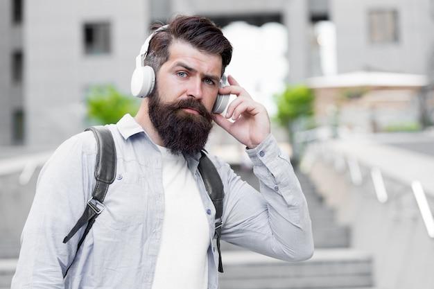 毎日のルートワーク現代の生活ヘッドフォンを持った男が市内中心部を歩く音楽を聴くハンサム