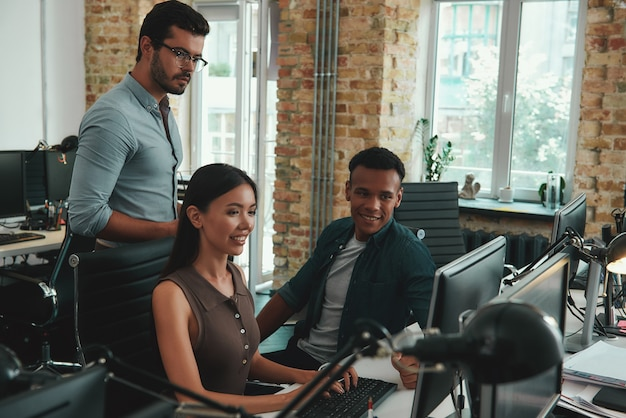 Ежедневная группа молодых сотрудников, работающих на компьютерах и обсуждающих результаты проекта, в то время как