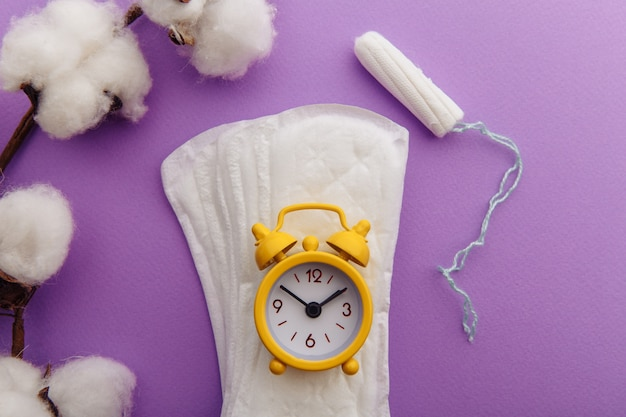 매일 위생 패드, 탐폰 및 노란색 알람 시계. 여성의 중요한 날을위한 위생 보호.