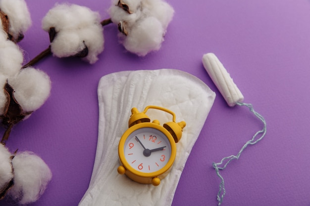 Daily sanitary pads, tampon and yellow alarm clock close-up. hygiene protection for woman critical days.