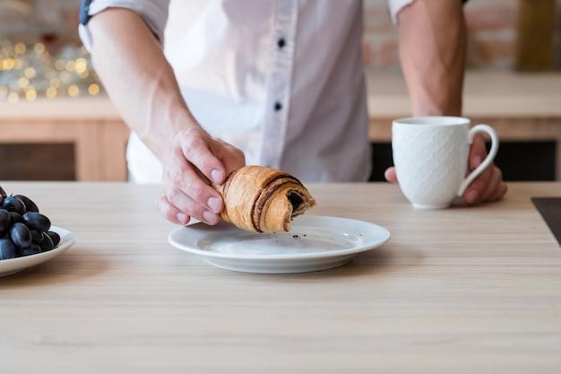 Ежедневный перекус. привычка к кондитерским изделиям. человек с чашкой напитка и круассаном. обрезанный снимок. кухонное пространство.