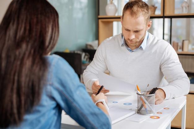 Дневная работа. серьезный сосредоточенный симпатичный мужчина, держащий лист бумаги и смотрящий на него, работая со своим коллегой