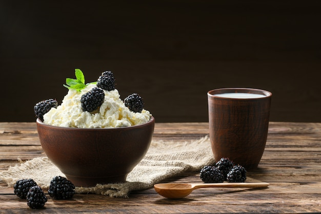 Dairy product cottage cheese and milk in brown ceramic bowl with spoon on wood