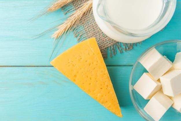 Молочные продукты. творог, сыр, молоко и кефир на синем деревянном столе с копией пространства.