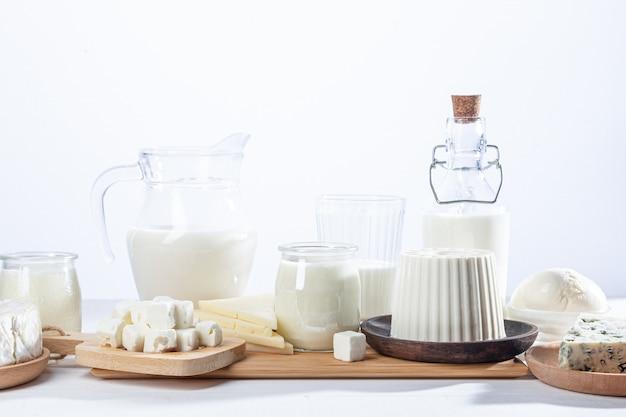 Молочные продукты в стеклянных получателях и деревянной посуде на белом фоне.