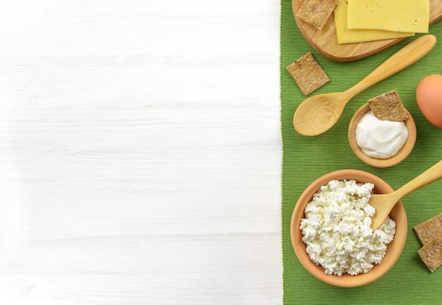 Молочные продукты в деревянной миске для здорового завтрака на белом деревянном столе. сметана, творог, яйцо, сыр. вид сверху с копией пространства Premium Фотографии