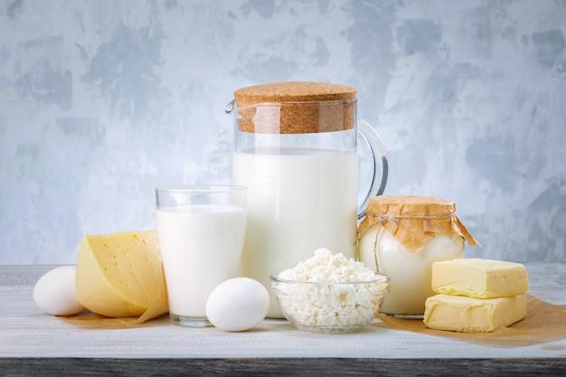 Молочные продукты, молоко, творог, яйца, сметана и масло на деревянном белом столе.