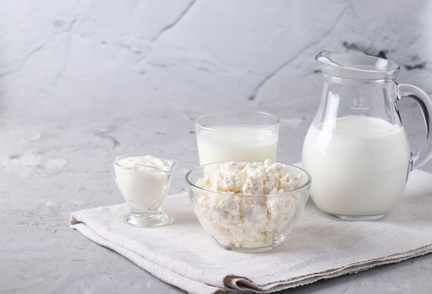 Dairy products: milk, kefir or ayran, cottage cheese and sour cream in a transparent bowl, jug and glass on a gray surface, space for text, closeup