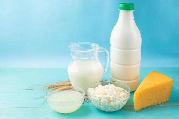 乳製品。青い木製のテーブルにミルク、ケフィア、カッテージチーズ、チーズ、ホエイ。