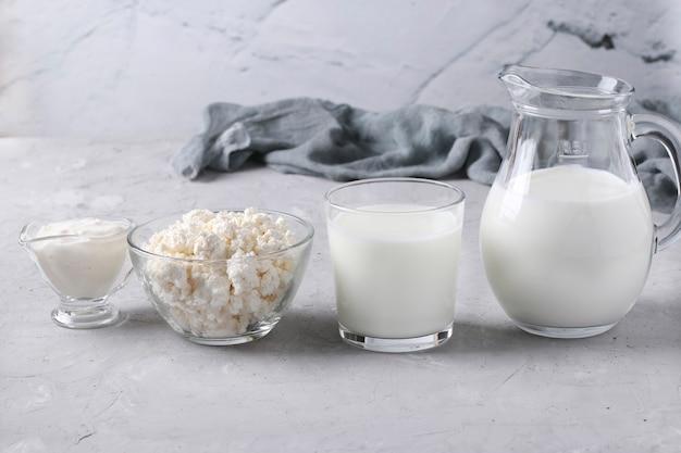 Молочные продукты молоко, кефир или айран, творог и сметана в прозрачной посуде.