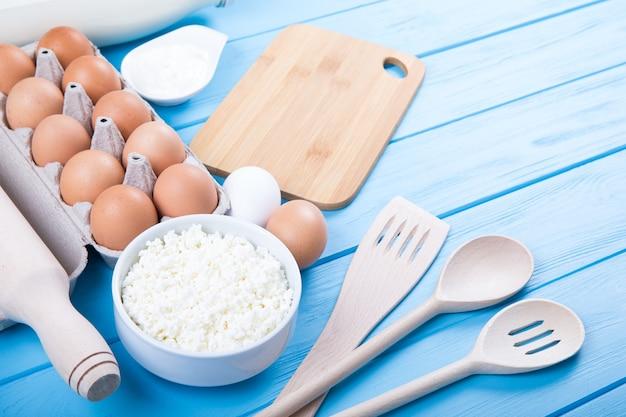 青い木製のテーブルの上の乳製品。サワークリーム、ミルク、チーズ、卵、バター。上面図