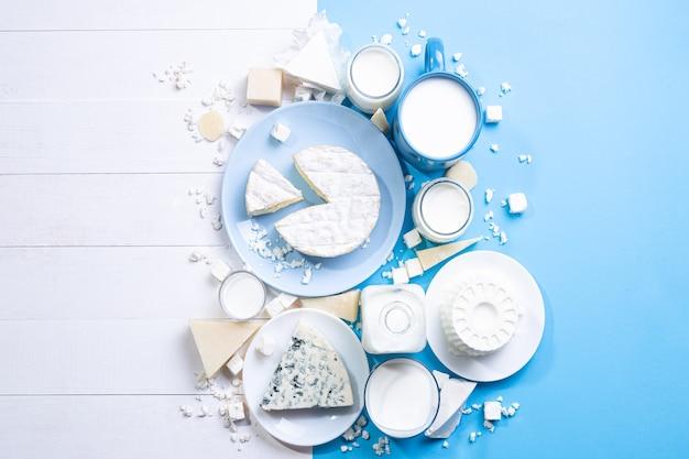 Молочные продукты на белой древесине и синем фоне с копией пространства. вид сверху, плоская планировка.