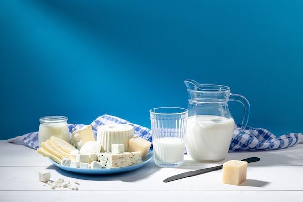 Молочные продукты на белой деревянной основе и синем фоне.