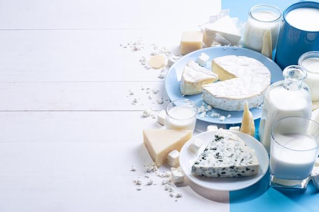 Молочные продукты на белой деревянной основе с копией пространства.