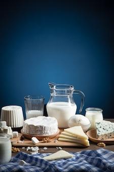 Молочные продукты на деревянной основе и синем фоне с копией пространства. вертикальный формат.