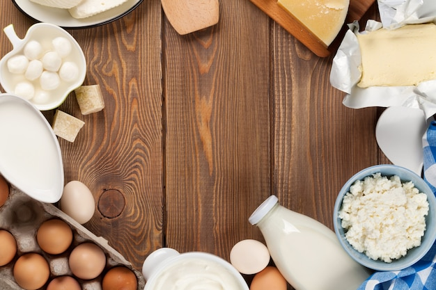 나무 테이블에 유제품입니다. 우유, 치즈, 계란, 두부 치즈 및 버터. 복사 공간이 있는 상위 뷰