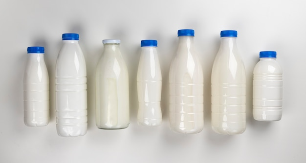 Упаковка молочных продуктов, бутылки и стаканы с молоком, изолированные на белом фоне