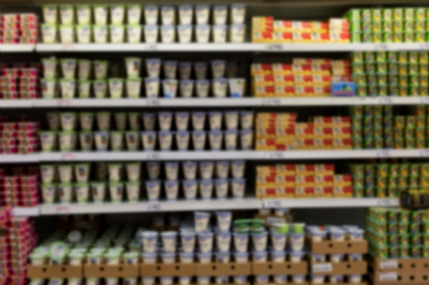 Dairy products on the shelves in the store. blurred.