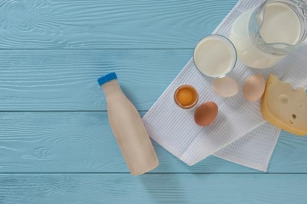 Молочные продукты с сыром и яйцами на синем деревянном фоне, вид сверху. концепция здорового питания