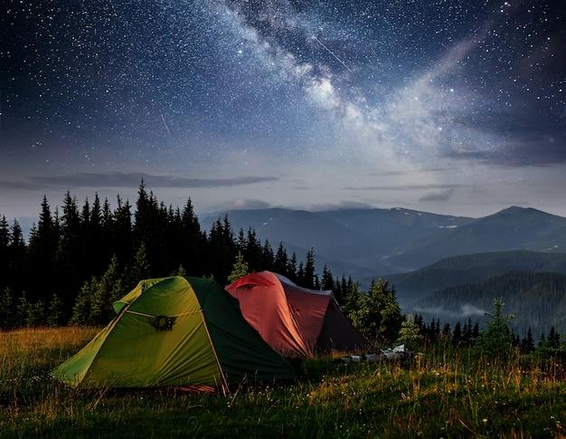 Молочный звездный путь над палатками. драматические и живописные сцены в ночных горах. карпатская украина европа.