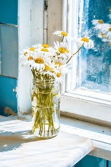 창 근처 테이블에 유리 항아리 꽃병에 데이지