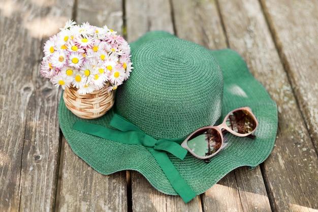 サングラスデザイナーの近くの緑の帽子の上に横たわっているデイジーは、牧草地の昔ながらの植物相の花束と...