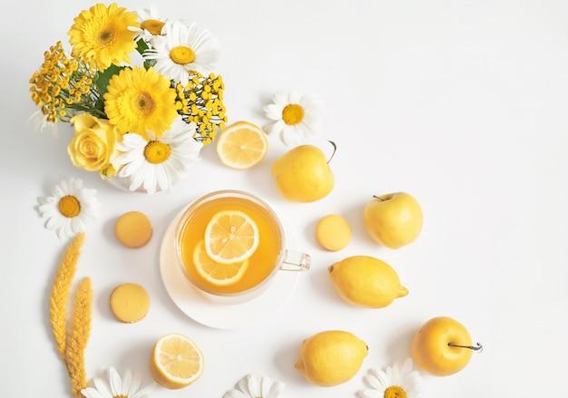 レモンスライスと花瓶に新鮮なカモミールの花のヒナギクティーカップ