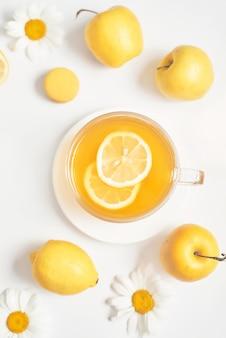 レモンスライスとヒナギクティーカップ。マグカップに生花カモミールとハーブティー。ビタミン、健康的な食事。代替医療と免疫ブーストの概念。
