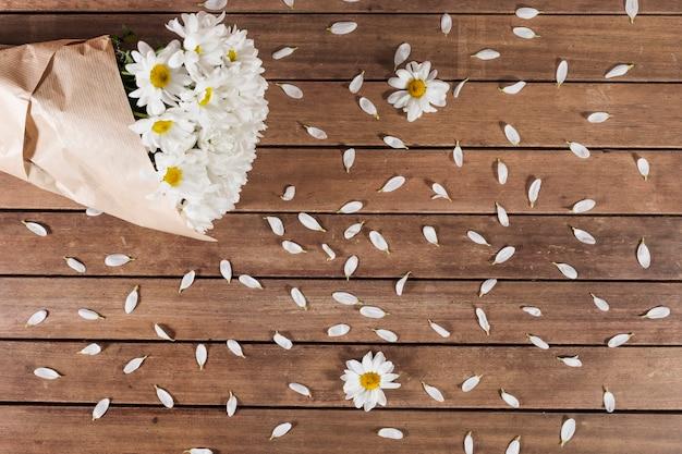 데이지 꽃다발과 나무 표면에 꽃잎