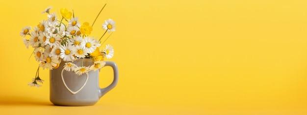 Цветы ромашки на серой чашке на желтом фоне баннера