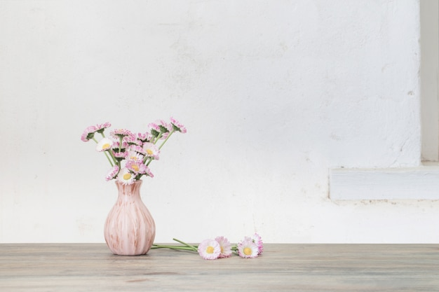 Daisy flowers in pink vase on wooden table