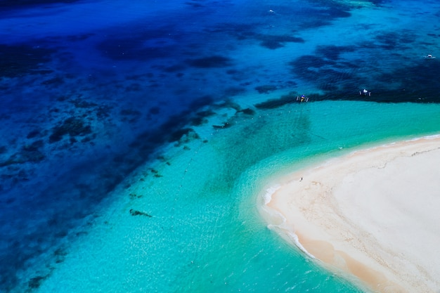 Daku island view from the sky. man relaxing taking sunbath on the beach.shot taken with drone above the beautiful scene. concept about travel, nature, and marine landscapes
