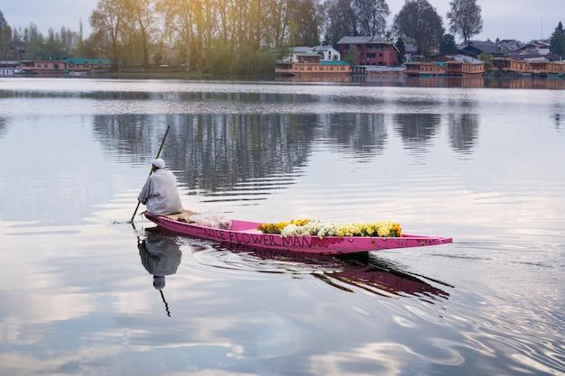 Dal湖のライフスタイル、男性がdal湖と山のバックグラウンドの真ん中でボートを運転する